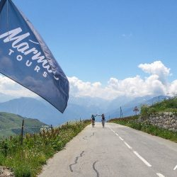 Marmot Tours guide welcomes rider to the top of the Madaleine on the classic cols of the alps road cycing holiday
