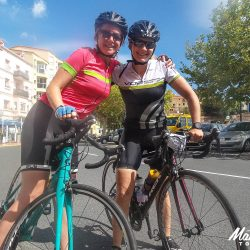 Two female cyclists celebrate at the finish of the marmot tours raid pyrenean