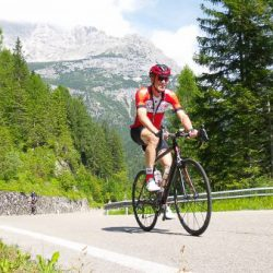 Happy cyclist cycling through pine forests in the Dolomites