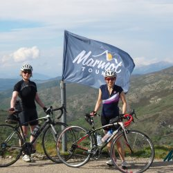 Flying the Marmot Tours flag on the Raid Sardinia with mountains behind