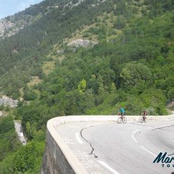 Cyclists taking on the 21 bends of the road cycling climb of l'Alpe d'Huez with Marmot Cycling Holidays