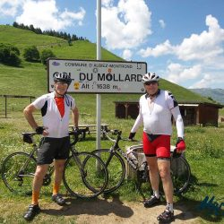 Two happy cyclists by the sign of the Col du Mollard on a Marmot Tours Road Cycling holiday in the Alps