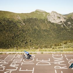 Loyal Marmot Tours client Jeremy reaches the summit of Pas de Peyrol and crosses the remnants of the TDF road paintings left by the local fans, riding the Raid Massif Central - rmc