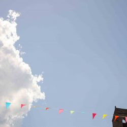 Blue sky, fluffy white clouds and bunting from the local village fete in the Cevennes region, on the Marmot Tours Raid Massif Central - rmc