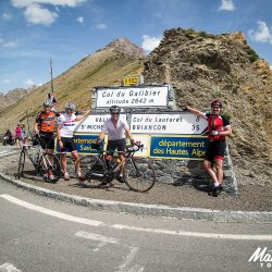 Posing for a photo at the summit of the Galibier with Marmot Tours on the raid alpine road cycling holiday.