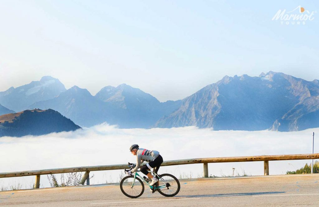 Cyclist above the clouds descending on Marmot Tours Alpine road cycling holiday