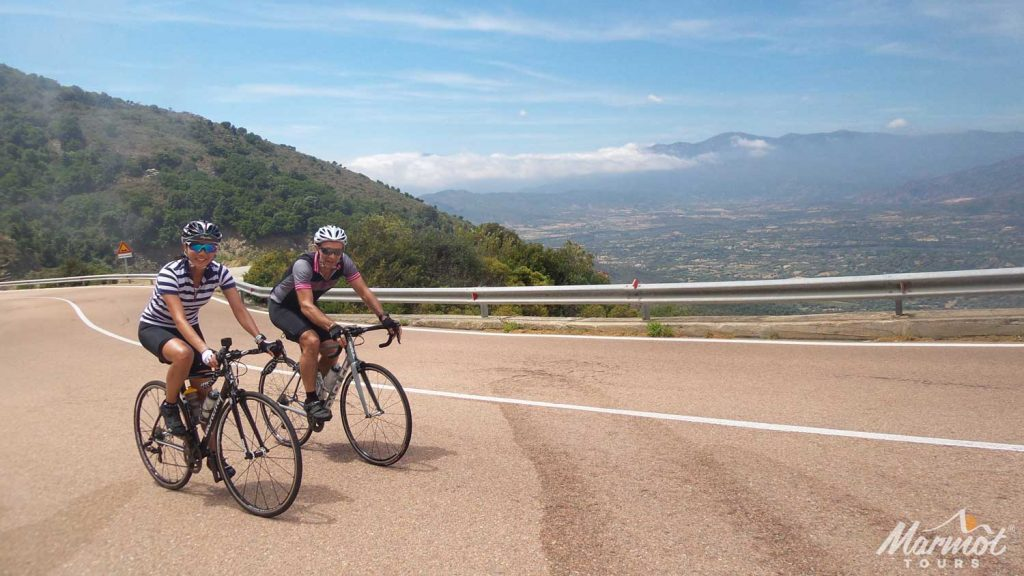 Couple enjoying great roads cycling in Sardinia with Marmot Tours