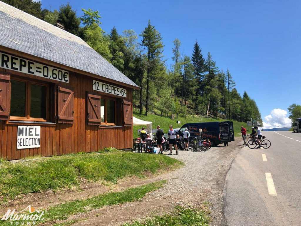 Cyclists at cafe on Col de Peyresourde Raid Pyrenean cycling challenge with Marmot Tours support van