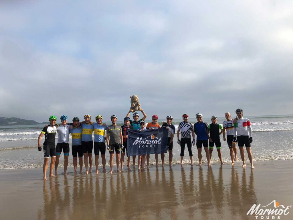 Group of cyclist in sea at start of Raid Pyrenean cycling challenge Marmot Tours