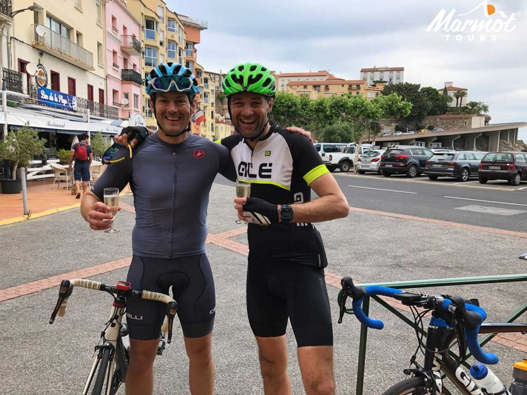 Two cyclists celebrating completing Raid Pyrenean cycling challenge with Marmot Tours