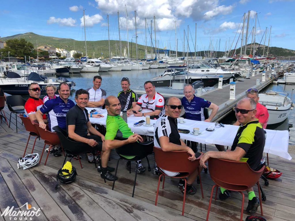 Cyclists enjoying dinner in harbour on guided road cycling holiday in Corsica with Marmot Tours