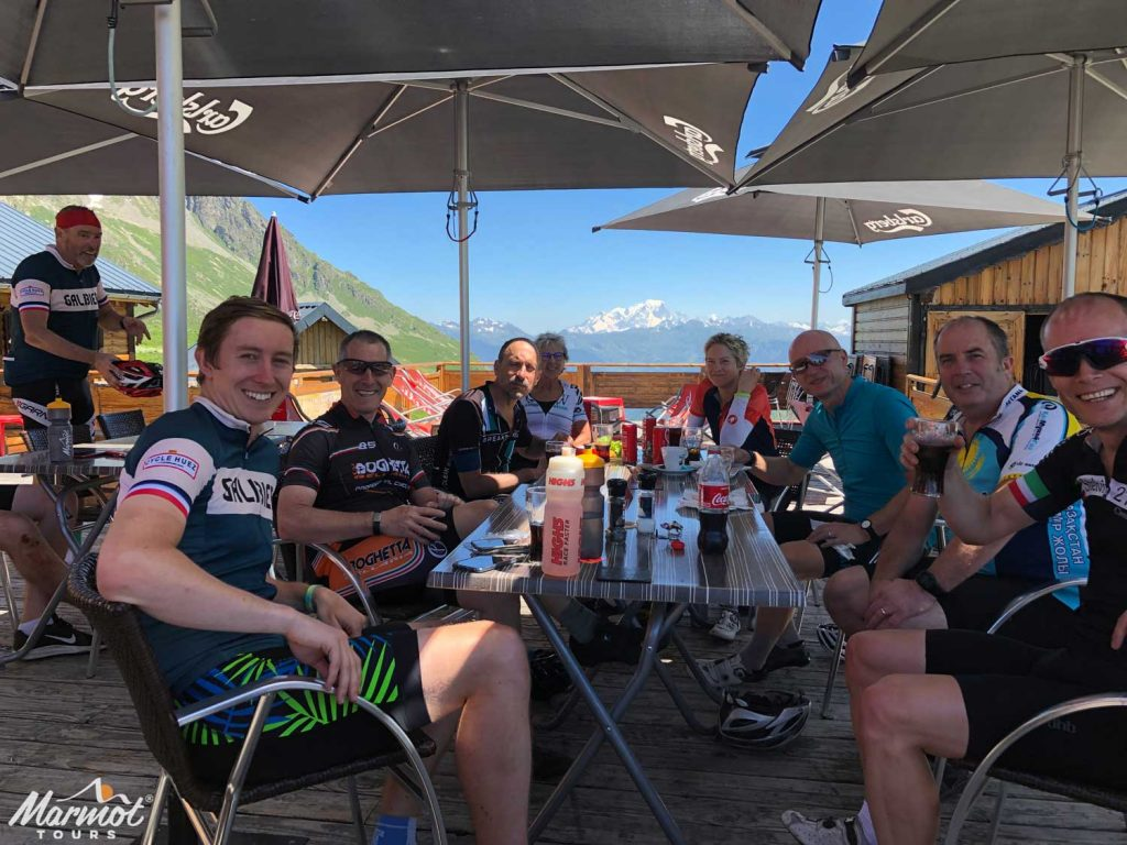 Cyclists with drinks at a bar with mountain views on Marmot Tours guided cycling holidays in the Alps
