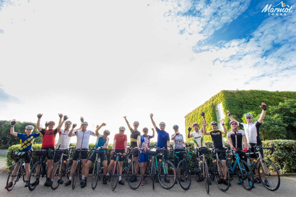 Large group of cyclists cheering at the start of Marmot Tours road cycling holiday in Europe