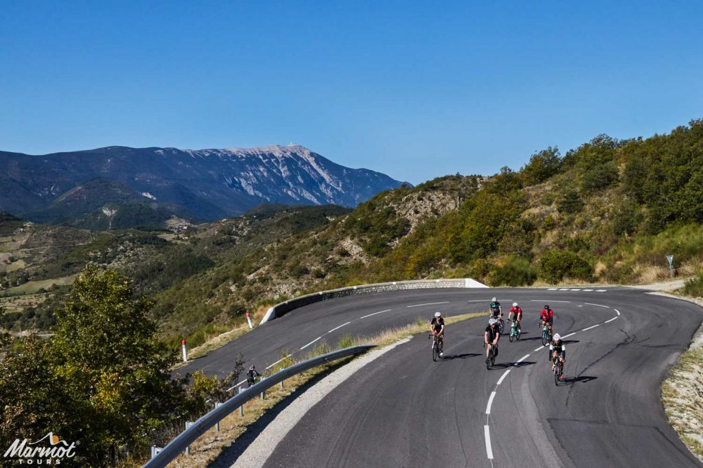 Group of cyclists climbing on hairpin bend Mont Ventoux background with Marmot Tours