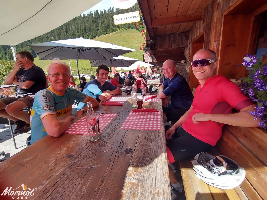Four cyclist enjoying a drink in Alpine cafe on Marmot Tours guided French cycling holiday