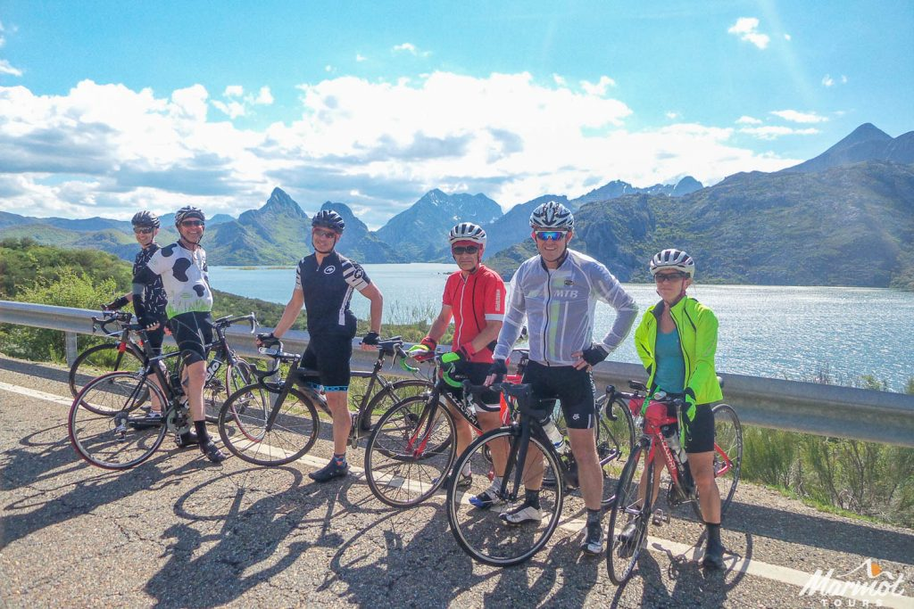 Group of cyclists posing for a photo by a lake on Marmot Tours fully supported road cycling holiday in Spain Picos