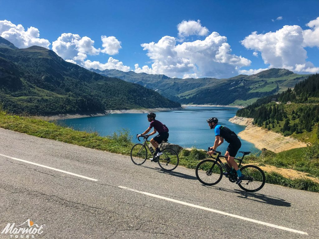 Pair of cyclists climbing in the alps with damn in background with Marmot Tours European road cycling holidays