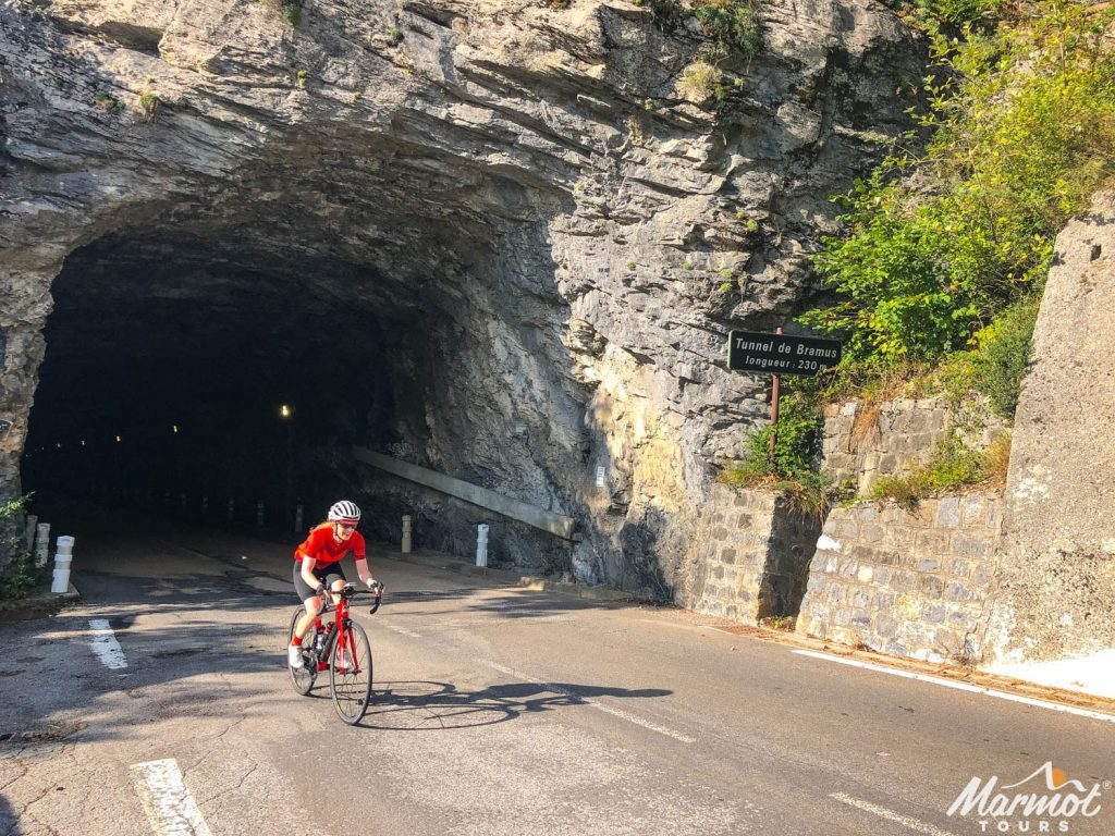 Female cyclist emerging from tunnel in the French southern alps on Marmot Tours European guided road cycling holiday